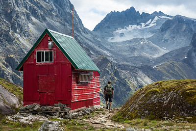 Backpacker Next to Wilderness Hut in Talkeetna Mountains, Alaska
