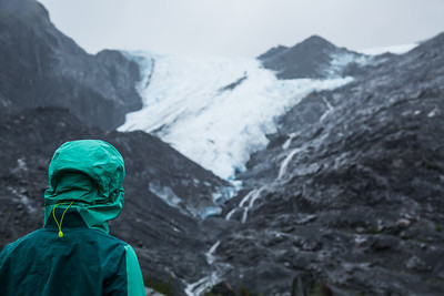 Woman in rain jacket on gloomy day looking at Worthington Glacier in Alaska