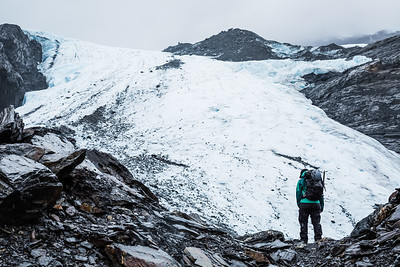 Woman walking in the rain on rocky moraine on the Worthington Glacier