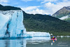 Kayaker paddling away from terminal face of the Spencer Glacier in Alaska