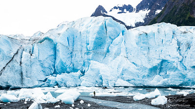 Man standing below massive glacier calving face