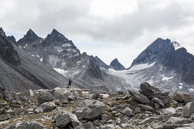 Man standing below huge cirque, glacier, and rocky peaks in the Talkeetna Mountains of Alaska