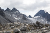 Man standing below huge cirque, glacier, and rocky peaks in the Talkeetna Mountains of Alaska