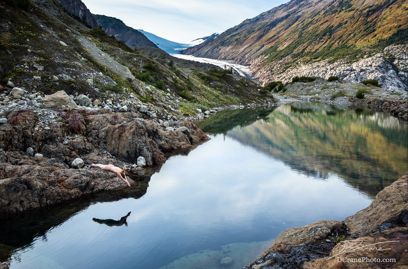 Young woman skinny dipping in calm pool in the Canadian mountains