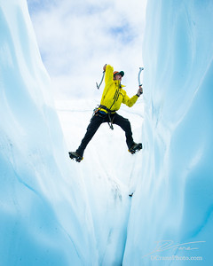 Ice climber with no rope spanning a crevasse swinging an ice tool