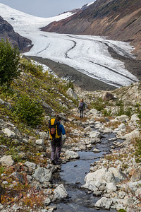 Man and woman walking along small stream toward Berendon Glacier in British Columbia