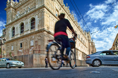 Cyclist in front of Sagrario Church, Constitution Avenue, Seville, Spain