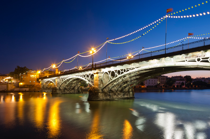 Triana bridge at dusk with decorative lighting for La Vela festival, Seville, Spain