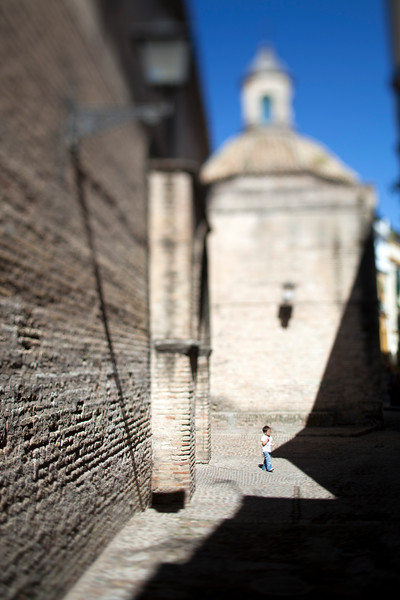 Child walking in front of Santa Marina church, Seville, Spain. Tilted lens used for shallow depth of field.