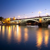 Triana bridge and Betis street at dusk with decorative lighting for La Vela festival, Seville, Spain