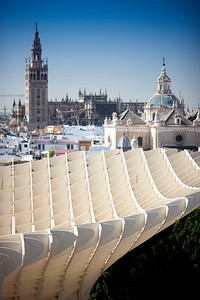 The Giralda tower (left) and El Salvador dome (right) as seen from the top of Metropol Parasol (foreground), Seville, Spain