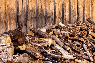 Unsorted wood pile against weathered wood-sided building.