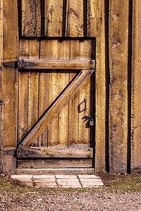 A heavy wooden door, locked from the outside, to an old wood-sided building.