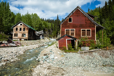 Two buildings standing and one collapsed by river in old abandoned alaskan mining town of Kennicott