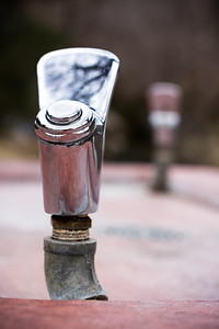Shallow depth double drinking fountains over red stone bowl
