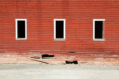 Three window frames on broken red wall of ghost town in Kennicott, Alaska