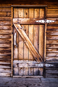 Old weathered wooden door to wood building, barn with lots of water damage to the wood.