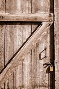 Close-up of wood door to an old house bolted shut with flat gold padlock.