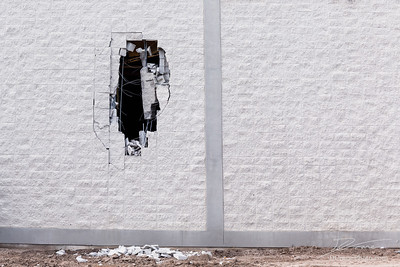 Brick wall being demolished with a big hole in it.