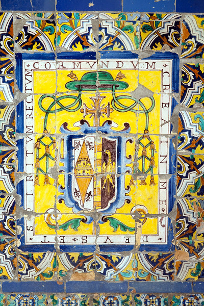Ecclesiastical badge on old glazed ceramic tiles, Fine Arts Museum, Seville, Spain