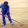 Bullring employee smoothing down the ground. Bullfight at Real Maestranza bullring, Seville, Spain, 15 August 2006.