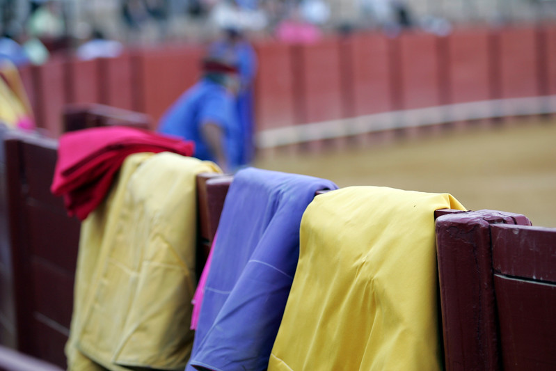 Bullfighter's capes on the burladero or barrier. Bullfight at Real Maestranza bullring, Seville, Spain, 15 August 2006.