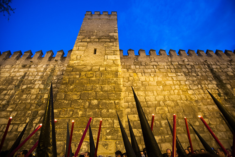 the cones of hooded penitents bearing candles against the Alcazar ramparts, Holy Week, Seville, Spain