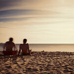 Two boys sitting on the beach and staring at the sea. Daylight long exposure shot by the use of neutral density filters.