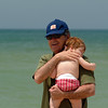 A grandfather holding his grandchild on the beach