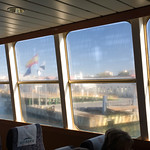 The flags of the European Union, Spain and Ceuta through a ferry window