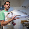 Fishmonger showing a big gilthead, Spain