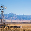 Old broken wind mill in front of big new wind farm in the Mineral Mountains of Utah