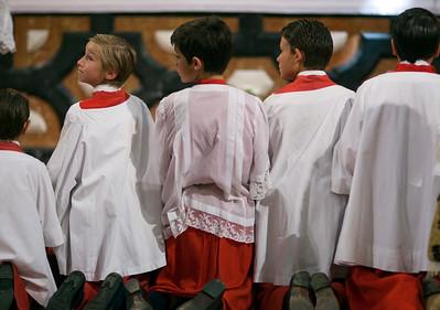 Kneeling altar boys praying at the end of Corpus Christi procession, Sagrario church, Seville, Spain, 2009.