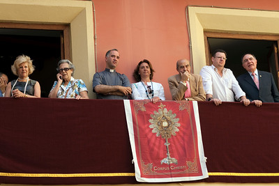People looking at Corpus Christi procession from a balcony with eucharistic ornaments, Seville, Spain, 2009.