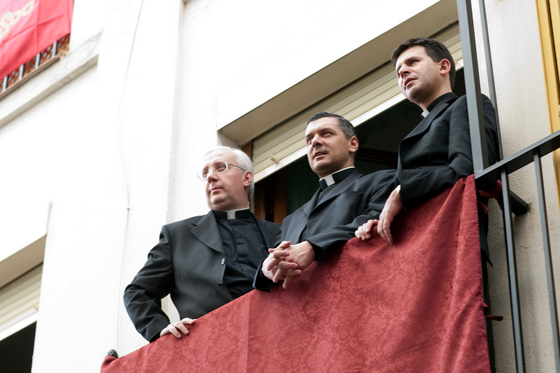 Three priests looking at Corpus Christi procession, Seville, Spain, 2009.