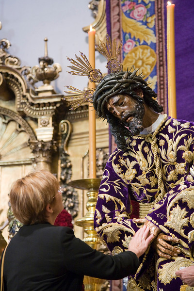 A woman touching the hands of Jesus del Gran Poder image, Seville, Spain