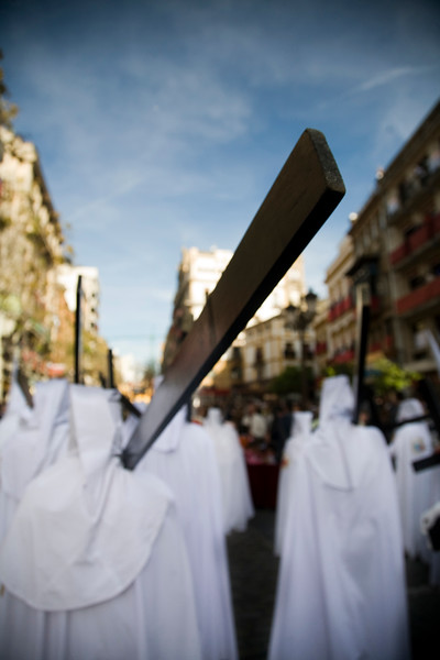Hooded penitents bearing wooden crosses, Palm Sunday, Seville, Spain