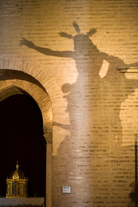 The shadow of a Resurrected Jesus Christ image on a wall of Santa Marina church, Seville, Spain