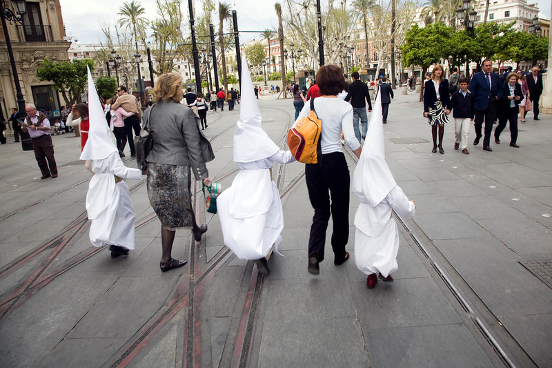 Two women leading young penitents to the church for a Holy Week procession on Palm Sunday, Seville, Spain