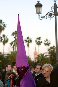 Hooded penitent with the Giralda tower on the background, Holy Week, Seville, Spain