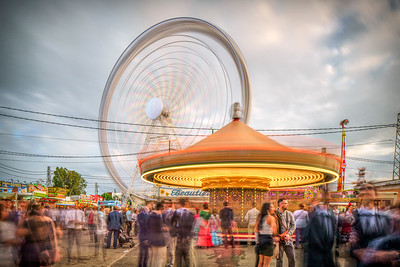 Carousel and Ferris wheel in a funfair, Feria de Abril, Seville, Spain. Long exposure shot.