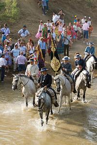 Riding pilgrims crossing the river