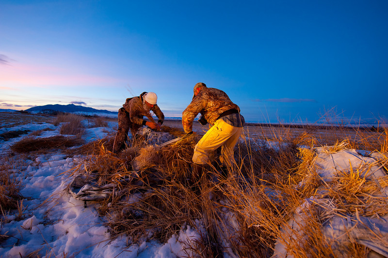 """Bret Seng and Dan """"Rooster"""" Leavens put the finishing touches on the blinds as the sun comes up."""