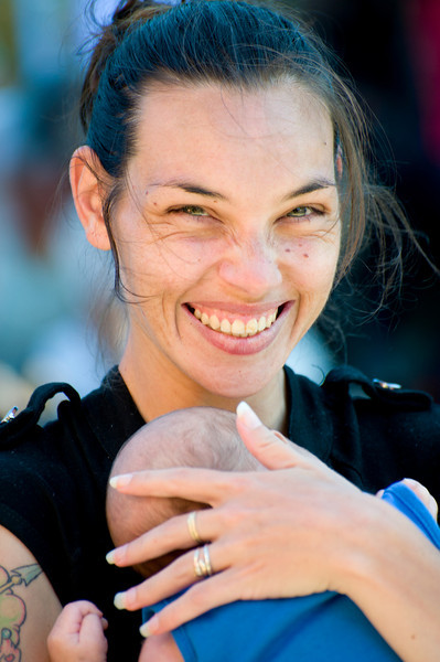 Happy Indigenous Australian Woman with her Baby Boy photographed outside on a blurred background