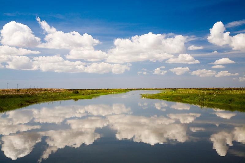 Nubes reflejadas en el río Guadiamar cerca de su desembocadura en el Guadalquivir. Isla Mayor (Sevilla), parque natural de Doñana.