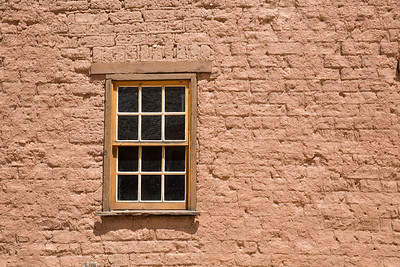 Old wooden window set into the red birck wall of a house in a ghost town in Utah.