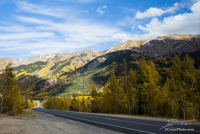 Back road through mountains with changing trees of Colorado