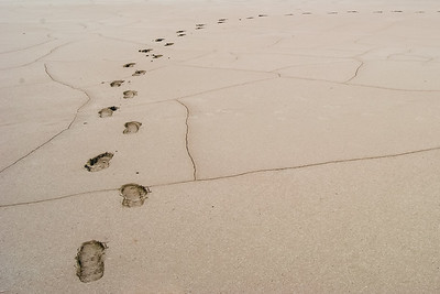 Footprints in deep soft sand curve to the right.