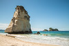 Tall white sea stack above sandy beach in New Zealand