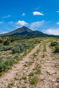 Dirt road trail through desert sagebrush toward small peak in the distance.